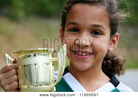 Young girl holding a trophy