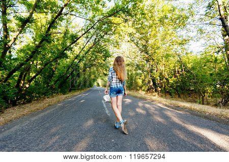 Beautiful Girl Walking On An Empty Road Between Green Trees