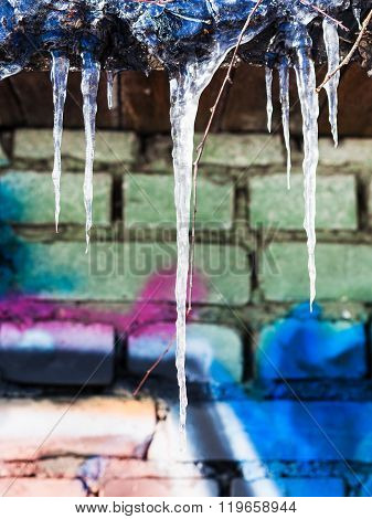 Icicles On Roof Of House With Painted Brick Wall