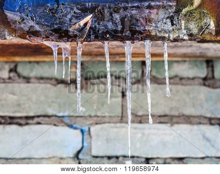 Icicles On Roof Of House With Brick Wall