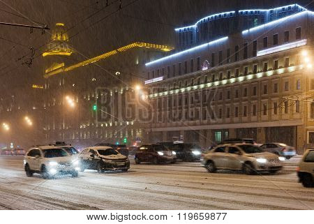Cars Driving Under Snow On Night Street