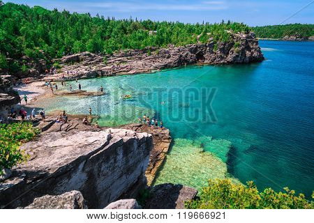 amazing natural rocky beach view and tranquil azure clear water with people in background on sunny b