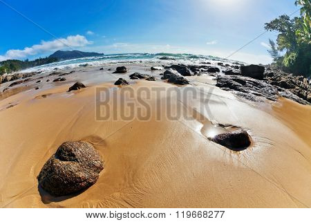 fisheye view on beach and tropical sea under blue sky
