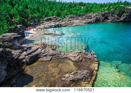 amazing natural rocky beach view and tranquil azure clear water with people in background