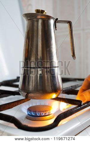 Hand Lighting The Gas Under The Coffeepot