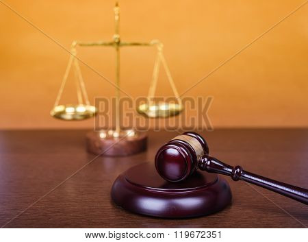 Wooden gavel with scale on wooden table, law concept