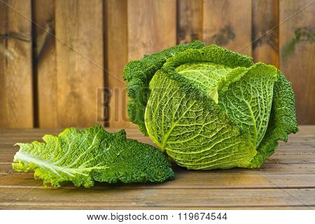 Single head of fresh green Savoy cabbage on wooden background