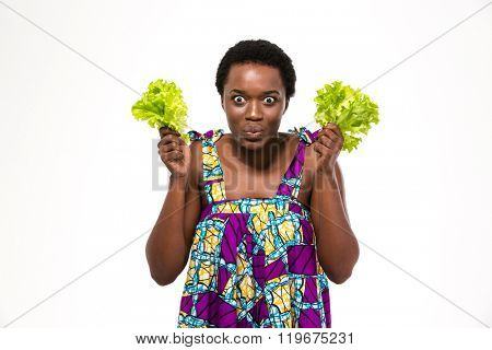 Funny excited african american young woman in colorful sundress holding leaves of lettuce over white background