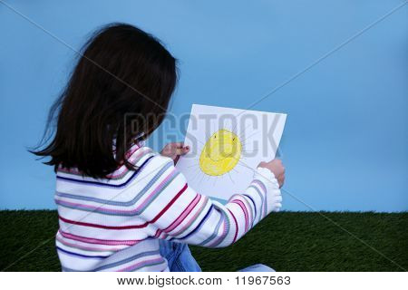 Young girl sitting in the grass holding a picture of the sun