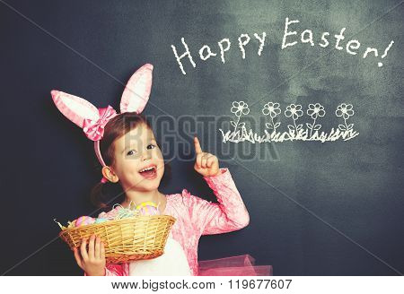 Happy Easter! Child Girl In  Costume Bunny Rabbit With Basket Of Eggs About Blackboard