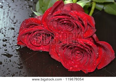 Three red roses on black wooden table with waterdrops