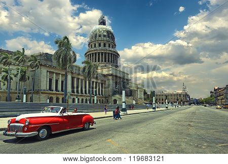 HAVANA, CUBA - July 10, 2015: Old classic american red car on the background of the National Capitol