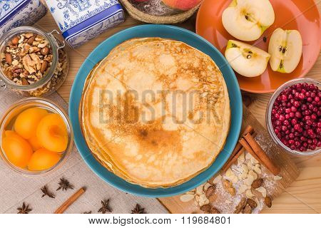 Golden pancakes in a blue plate top view