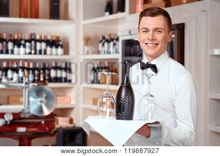 Pleasant sommelier holding tray with wine bottle