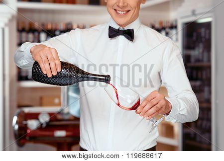 Pleasant sommelier pouring wine into wineglasses