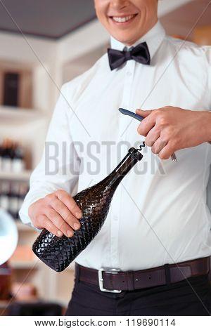 Professional sommelier opening bottle of wine
