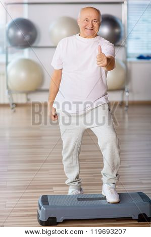 Pleasant senior man practicing step aerobics