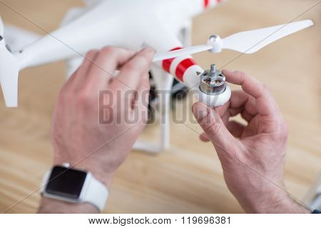 Cheerful young guy is adjusting a quadrocopter