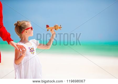 Adorable little girl with toy airplane in hands on white tropical beach