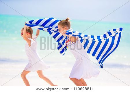 Little girls having fun running with towels on tropical beach with white sand and turquoise ocean wa