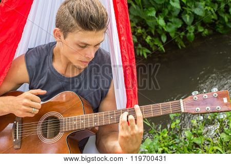 Young Man Composing Music With A Guitar In A Hammock In The Forest.