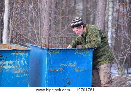 The image of tramp near the garbage bin