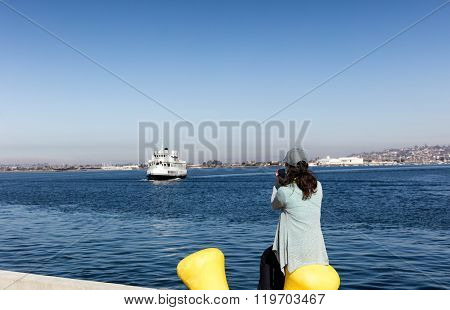 Woman Taking Photos Of The Bay Of San Diego While Sitting Down At Pier