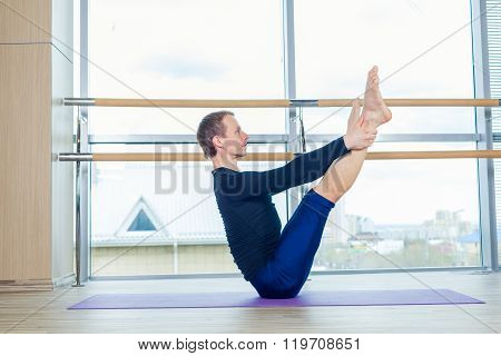 Sporty young man working out, yoga, pilates, fitness training, standing in asana eka pada adho mukha