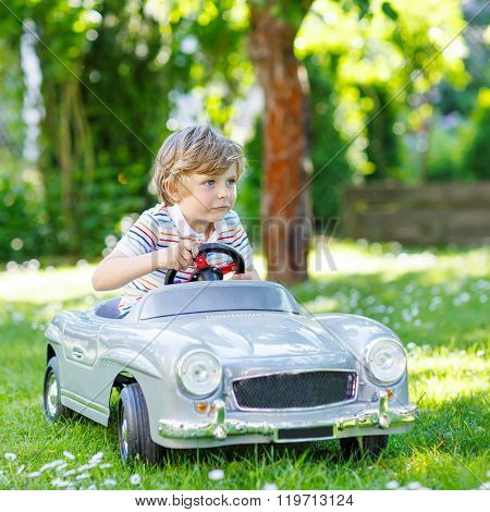 Kid boy driving with big toy car outdoors