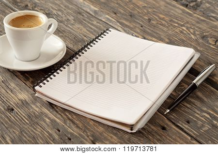 Open Notebook With A Pen And Cup Of Espresso Coffee