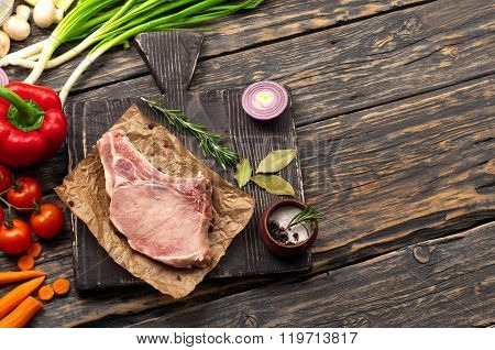 Raw Bone Steak On Paper With Vegetables