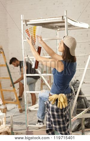 Young woman looking at color scale at home renovation.