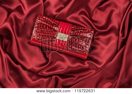 Red Lacquer Bag Inlaid With Diamonds Lying On A Red Silk