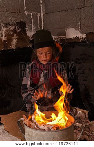 Dirty Homeless Boy Warming At The Fire