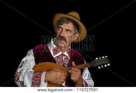 Portrait of Ukrainian country-man in traditional clothing playing mandolin