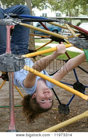 A school girl playing on a jungle gym during recess.