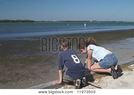 A boy and girl kneeling on a seawall at the water's edge.