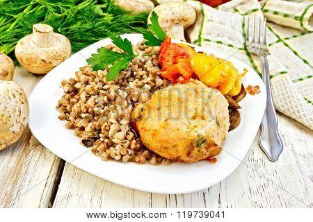 Cutlets of turkey with buckwheat in plate on board