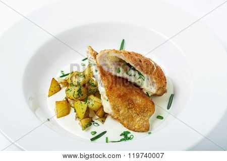 Cutting cordon bleu with cheese, turkey, crackers crumbs, potatoes.