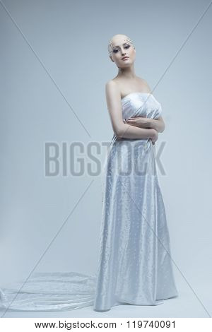 Studio portrait  beauty bald girl on a sky blue background.