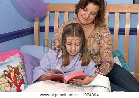 A mother and daughter reading the bible and bedtime