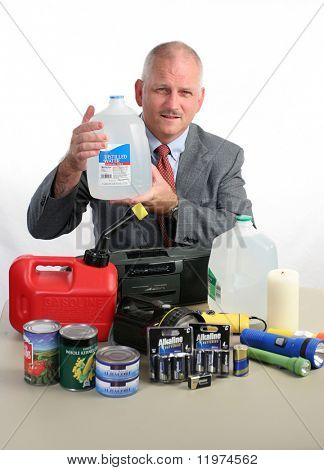 a meteorologist with hurricane supplies, holding up a jug of water