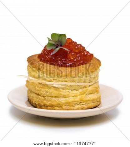 Tartlet with red caviar on white.