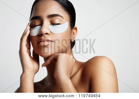 Woman With An Eyes Patches Touching A Face