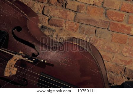 Old Contrabass Near Brick Wall.