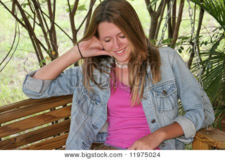 A beautiful teen girl on a porch swing, laughing and looking down.