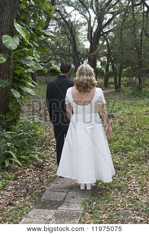 A newlywed couple headed down a wooded path.