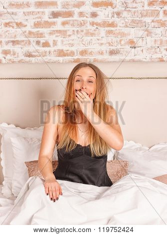 Young girl yawning in bed