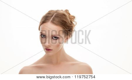 Young grumpy adorable blonde woman with cute fresh makeup posing with bare shoulders on white studio