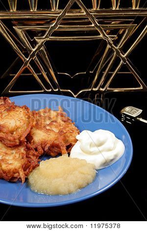Potato latkes for Hanukah with a menorah & dreidel on a black background. Vertical orientation.